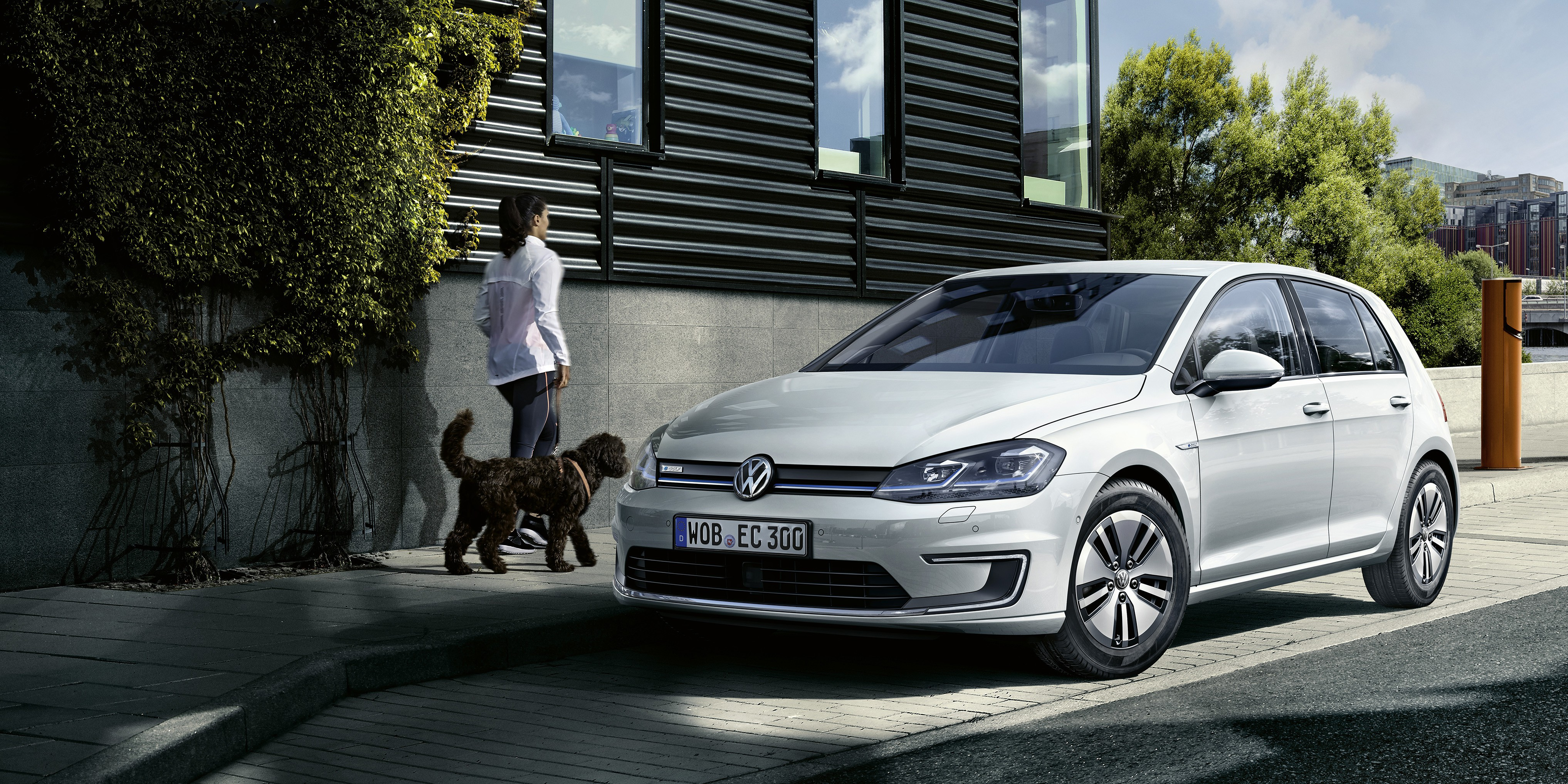 e-Golf on street with woman walking beside it with dog